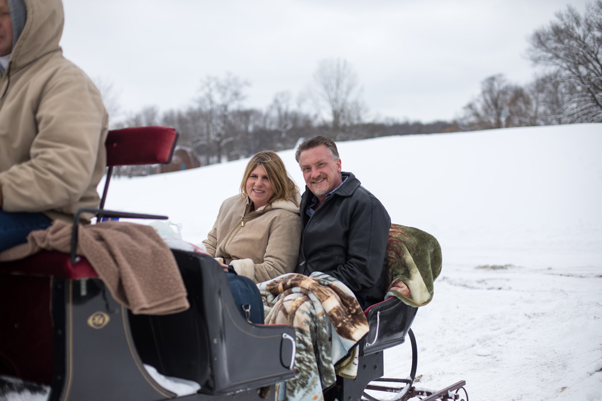 A man & woman enjoy a horse drawn carriage ride through the snow.