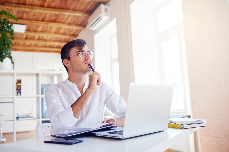 unschlüssiger Unternehmer am Schreibtisch