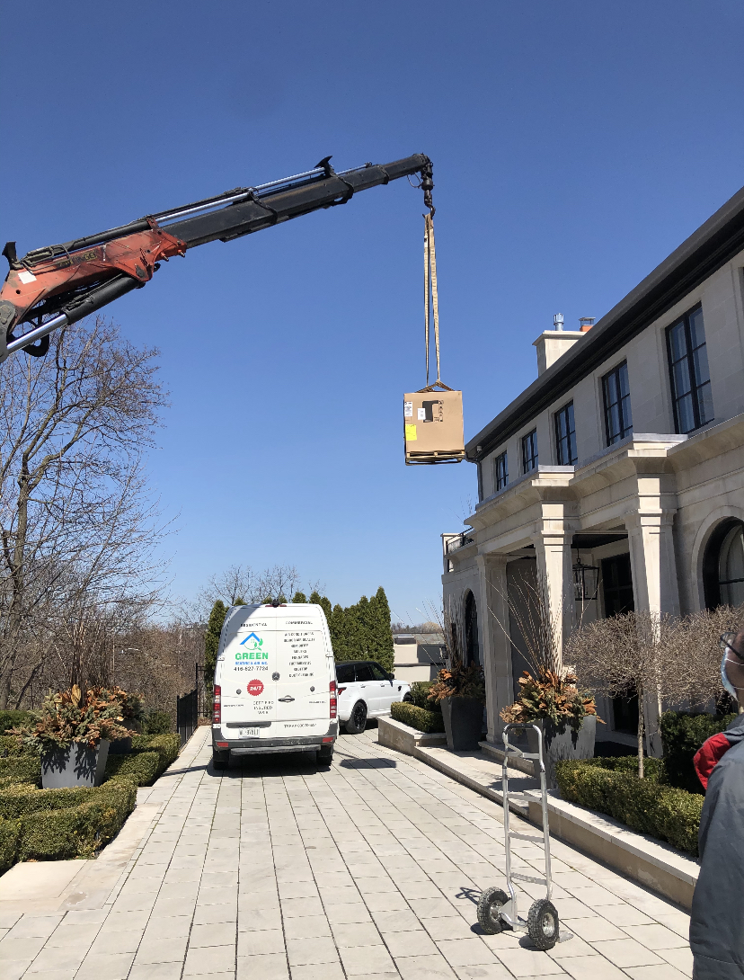 Green Heating and Air using crane to lift air conditioning unit to the roo