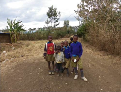 Children following us as we walk to visit families in their shanties (to the left) at GIWA.