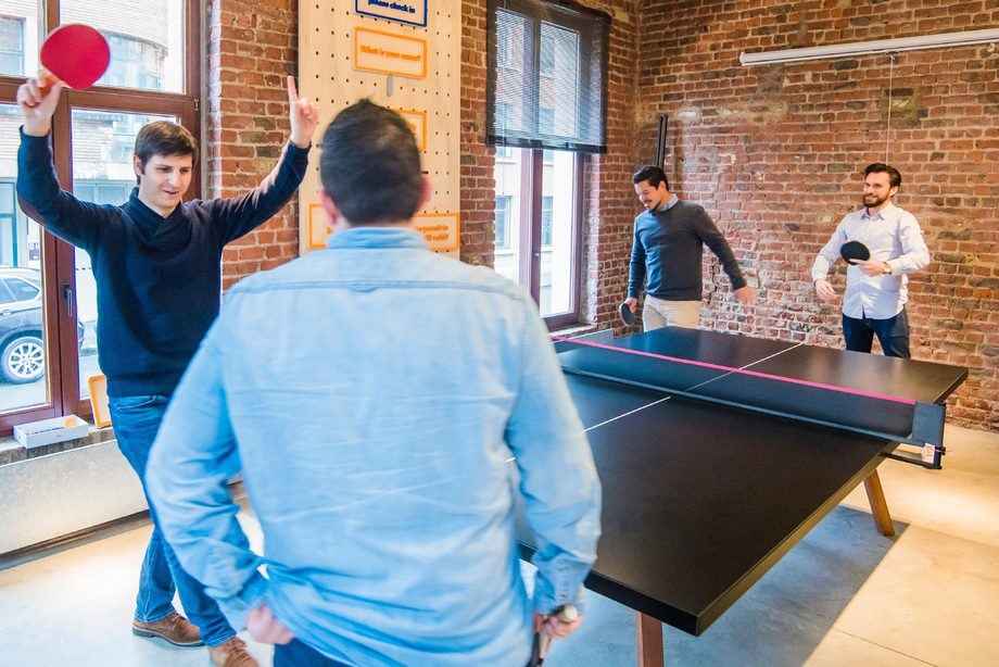 4 male colleagues playing ping pong