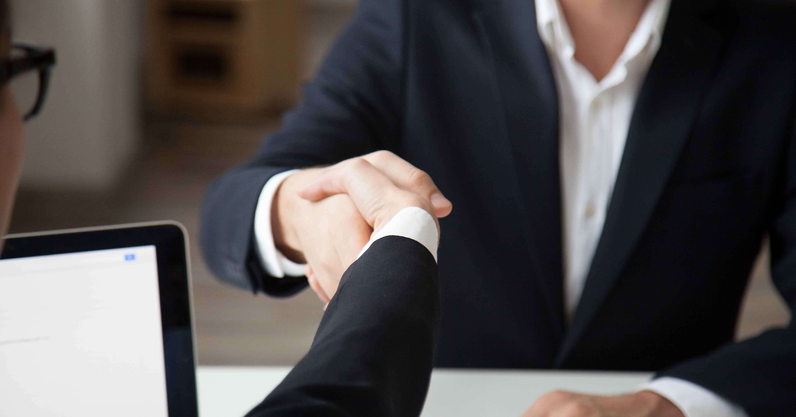 Business partners are shaking hands to reach an agreement