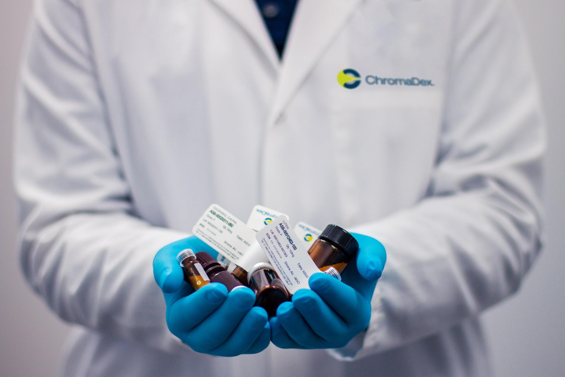 doctor holding a bunch of medicine bottles