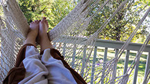 a happy customer relaxing in her Crysalis Hammock Chair on her deck on a sunny day