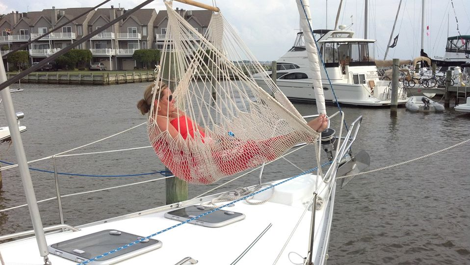Happy customer soaking up the sun in their hammock chair on the bow of a boat