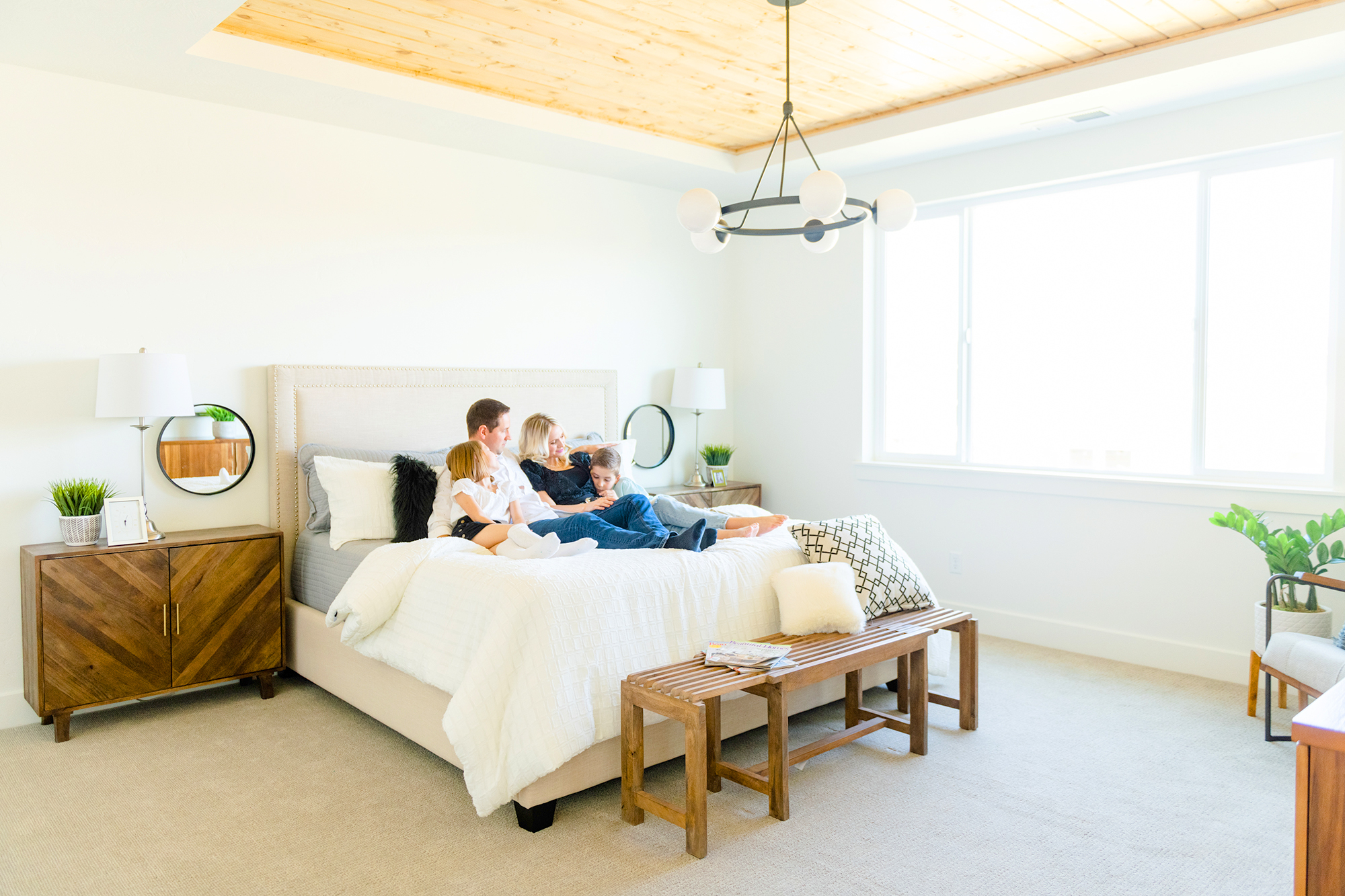 Berkeley Building Co. Contact Us hero image of family relaxing in bed together.