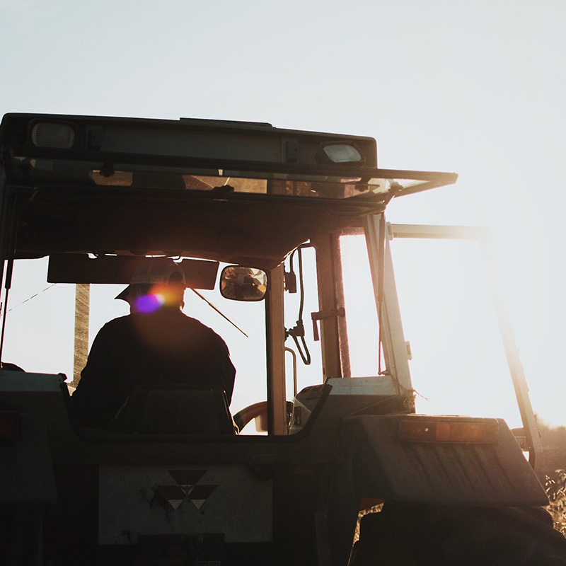 Trident Farmer on a tractor at sunset