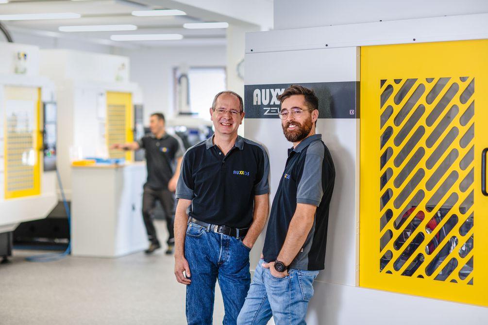 Die Gründer der AUXXOS GmbH, Andreas Koschnik und André Le Guin lehnen am Laserbearbeitungszentrum ASKIAS Precision