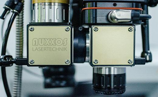 Ein AUXXOS Laserkopf in der Nahaufname mit dem AUXXOS Logo