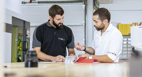 Zwei AUXXOS Mitarbeiter diskutieren angeregt über einem neuen Entwurf