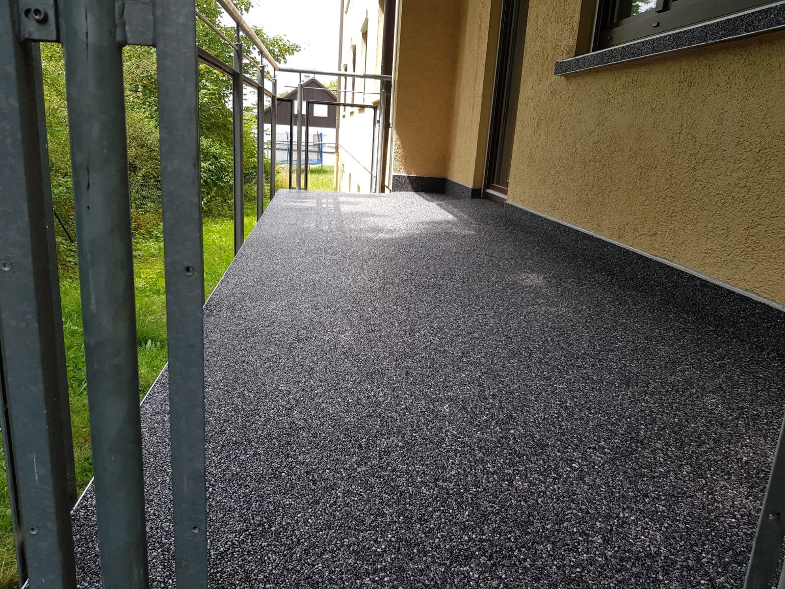 Ein Balkon mit einem grauen Steinteppich . Im Hintergrund ist etwas Garten zu sehen