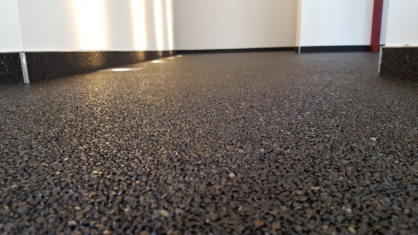 Ein schwarzer Steinteppichboden in einem Innenraum.