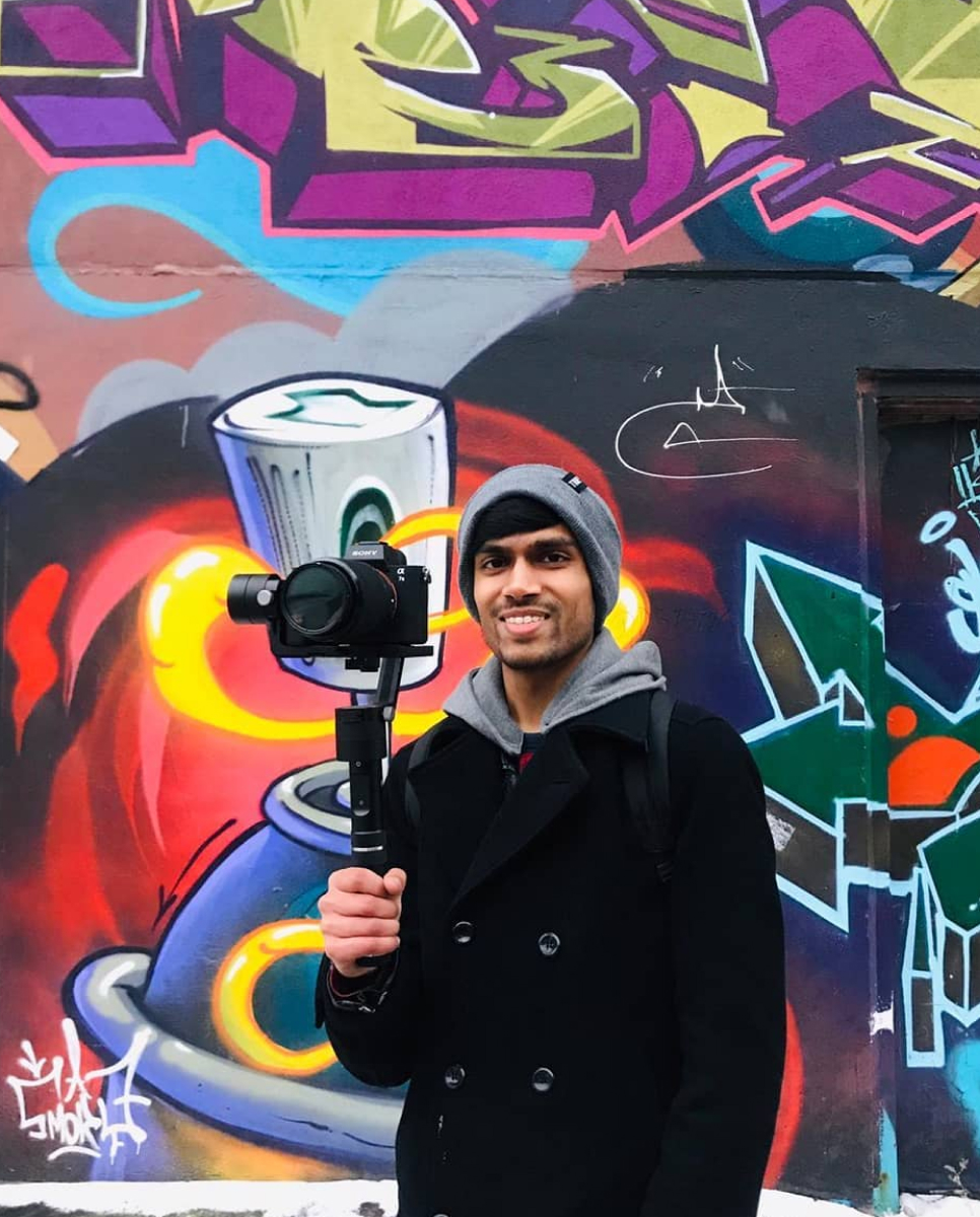 Vinit holding a camera stabilizer while standing in front of graffiti art