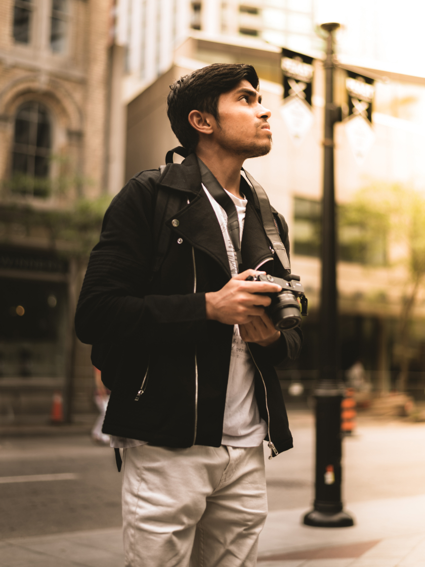 Vinit holding a camera while posing