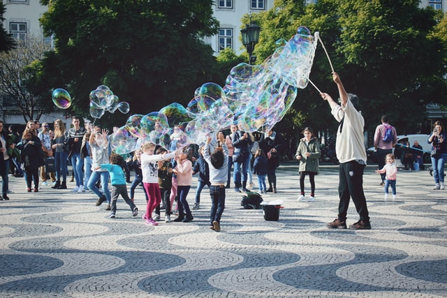A person making huge bubbles for children in a park