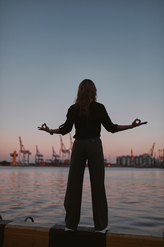 Julia standing near sea, doing a relaxation exercise with a yoga-like stand