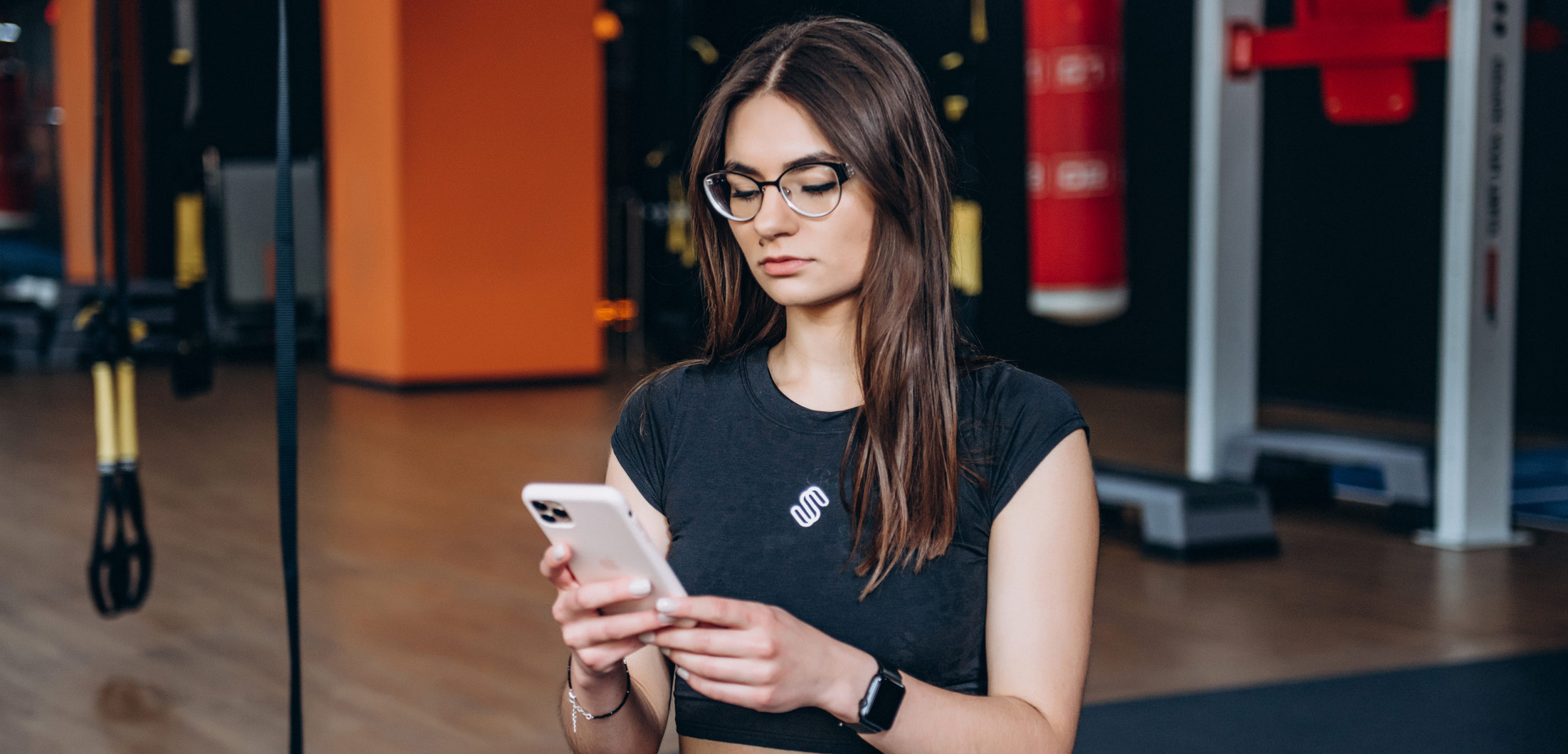 A personal training client looking at a fitness program on their phone