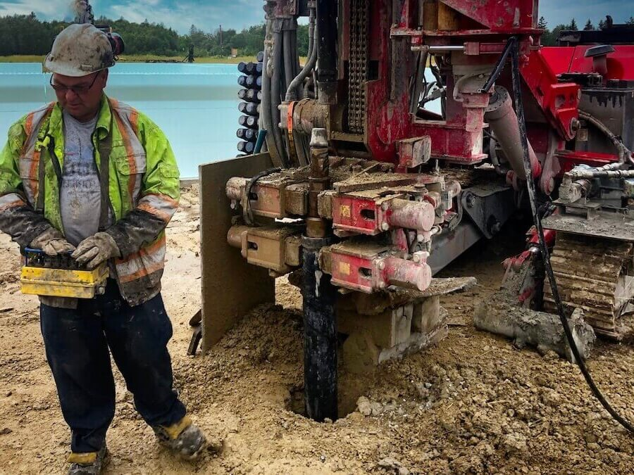 A well technician deepening a well for better water flow using well drilling machine.