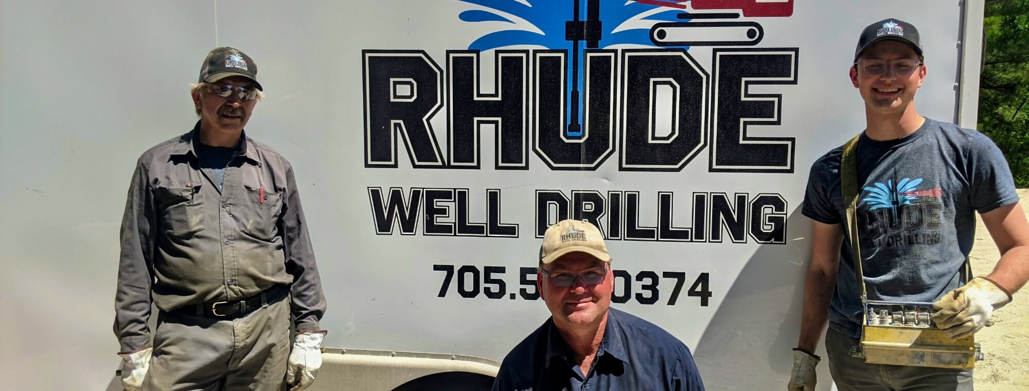 A few of the Rhude Well Drilling technicians smiling in front of a company trailer before starting a job.