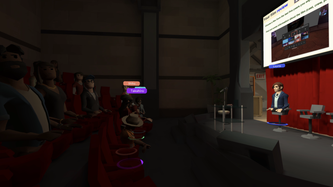 A virtual reality scene in a small theatre with a teacher presenting to a group of students