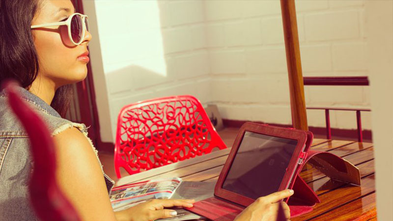 Image of a young woman in white sunglasses in front of a wooden table holding a tablet in a red case