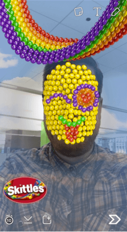 A man using the Skittles Pawn Snapchat lens; a Skittles rainbow floats over his head and cover his face