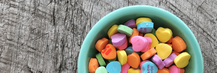 A turquoise bowl on a wooden table full of multi-color love hearts candy