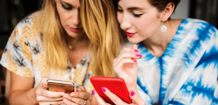Two women in brightly patterned tops standing shoulder to shoulder while looking at their mobile phone screens