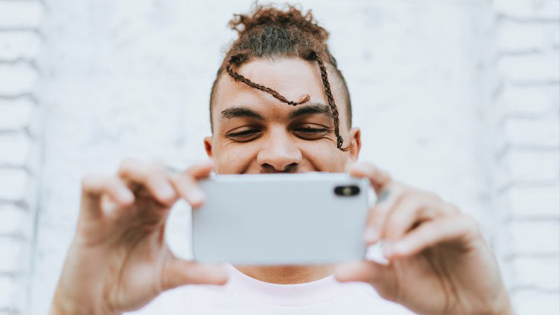 Image of a man with braids holding a white mobile phone while taking a picture