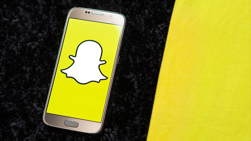 Mobile phone displaying an image of the Snapchat Ghost icon on a graphic black and yellow background