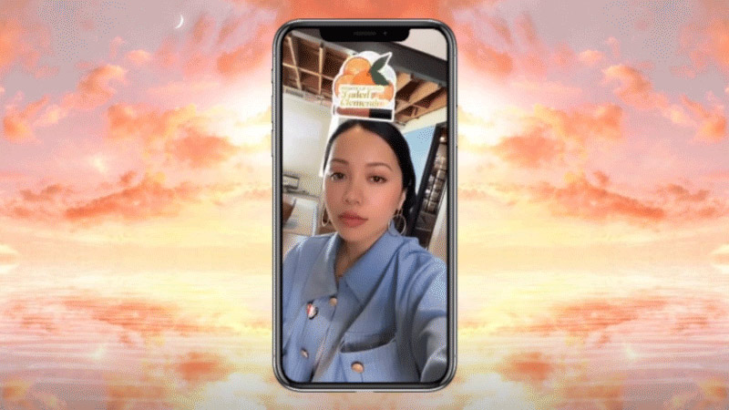 EM Cosmetic's founder Michelle Phan featured inside a mobile phone on a pink sky background using the Which Lip Cloud Randomizer filter