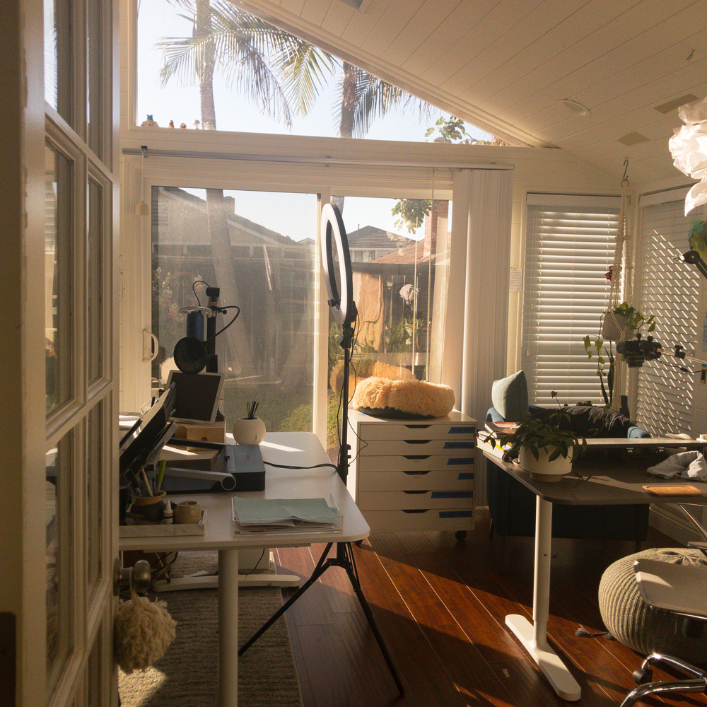 Image of a well-lit studio, filled with the most essential tools for a graphic designer and artist filling with warm light from the southern california sun.