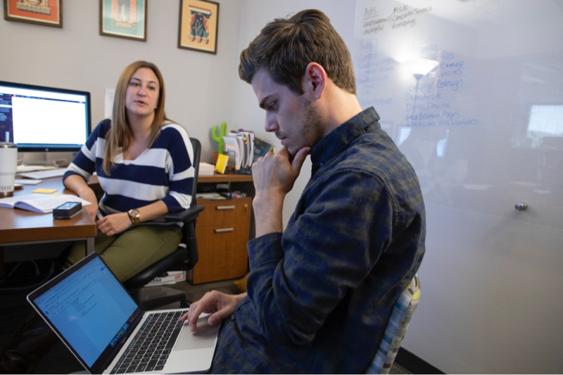 Chris taking notes on computer with team member