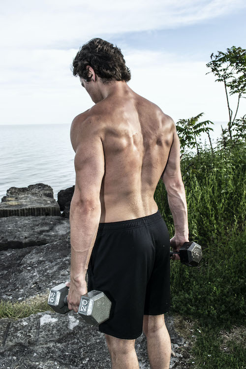 Image of Marshal McKenzie holding dumbbells showing his back muscles.