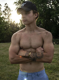 This is a picture of Marshal McKenzie posing staring at the camera shirtless.