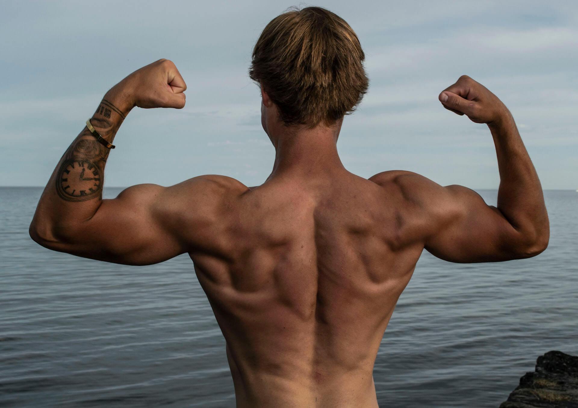 Keaton Ellis flexing his back in the 3 day split workout article.