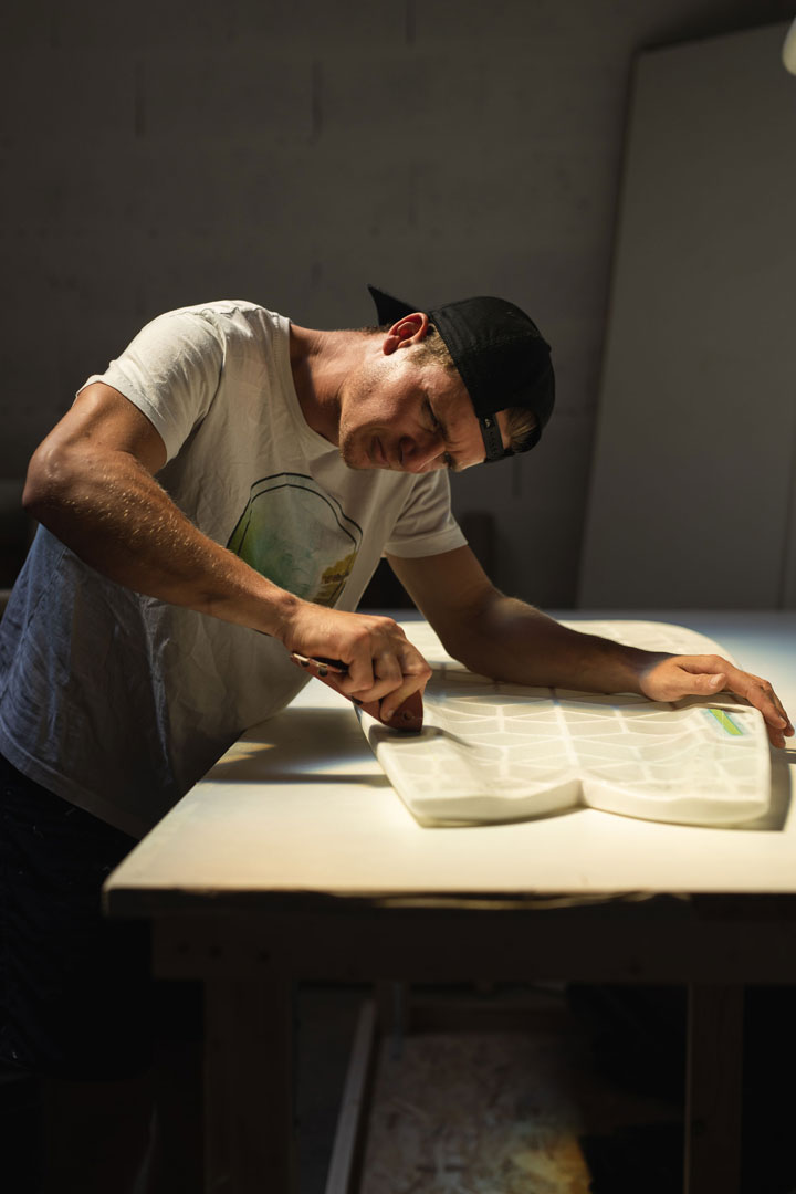 male local shaper sanding Wyve fish Hexa surfboard in micro-factory