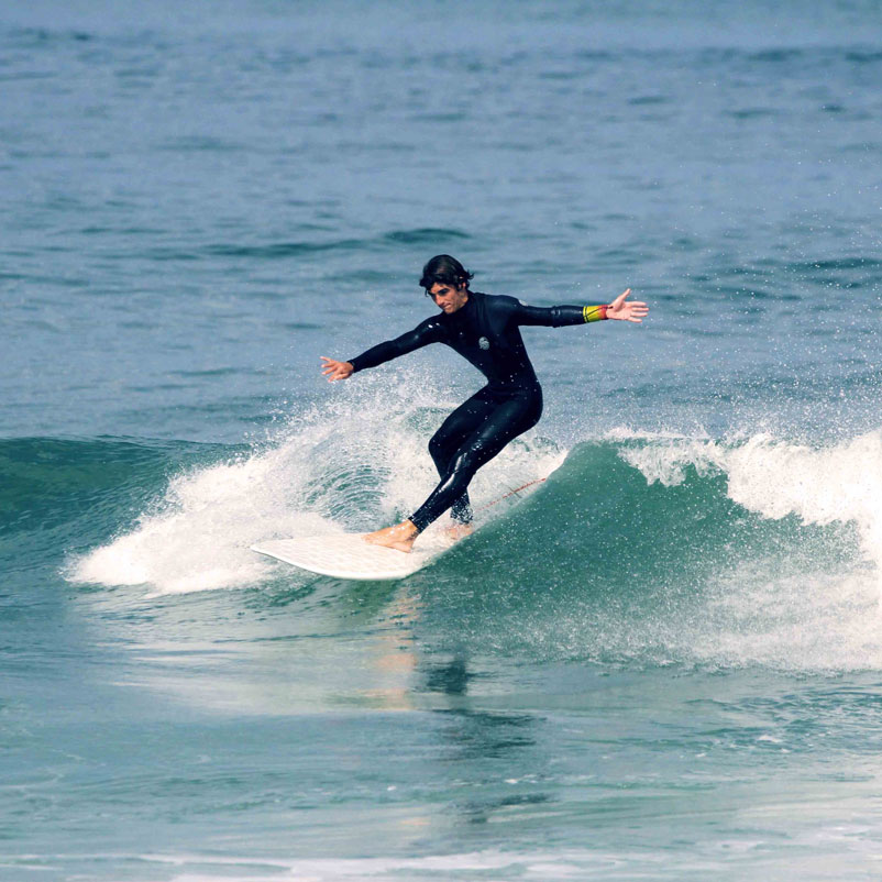 male surfer in perfect balance on green wave surfing Wyve white hexa surfboard