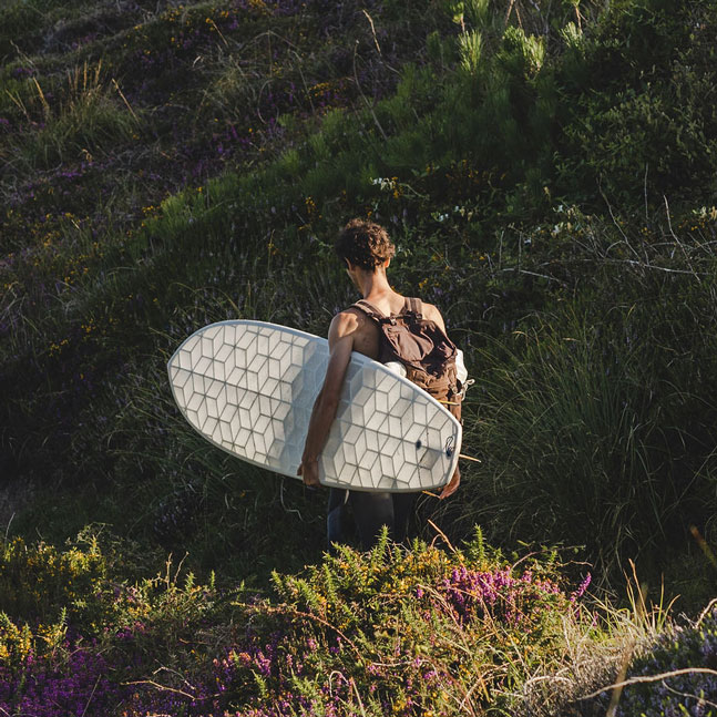 surfer walking in green nature holding his Wyve 3D printed surfboard