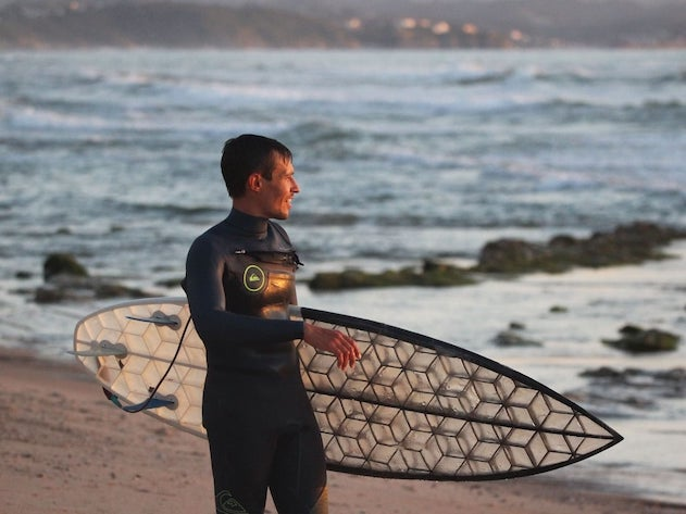 male surfer walking on beach with Wyve custom 3D-printed surfboard with performance shape