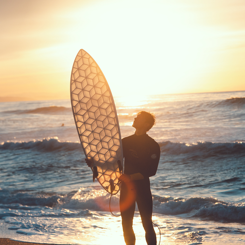 smiling surfer holding high his wyve mini simmons transparent surfboard with pride