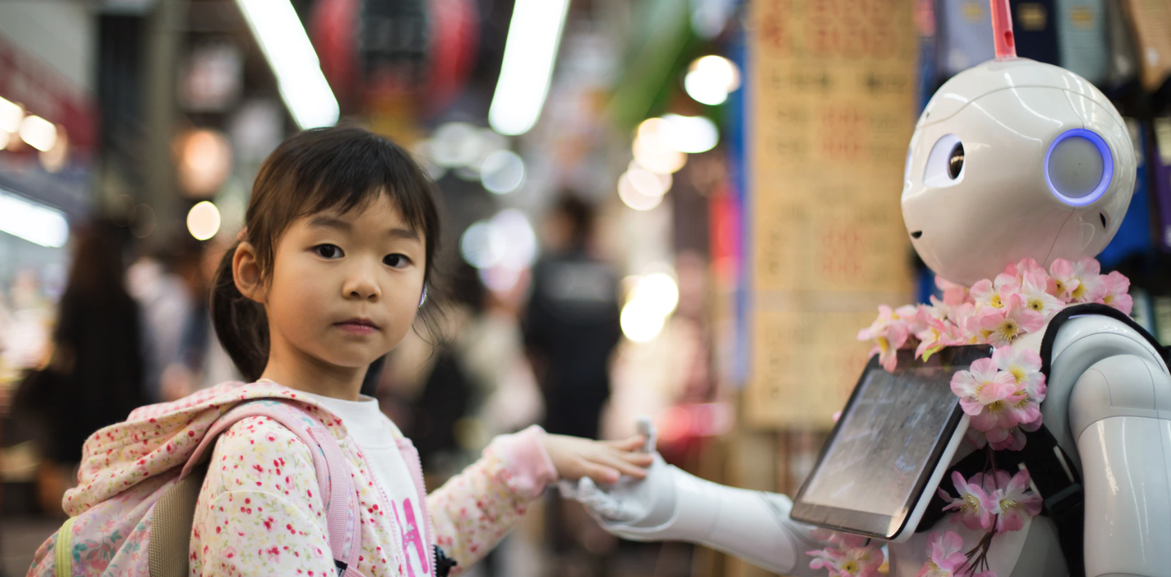 little girl holding hands with a robot