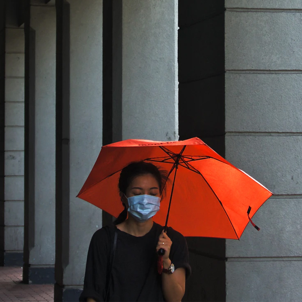person with a mask on and holding an umbrella
