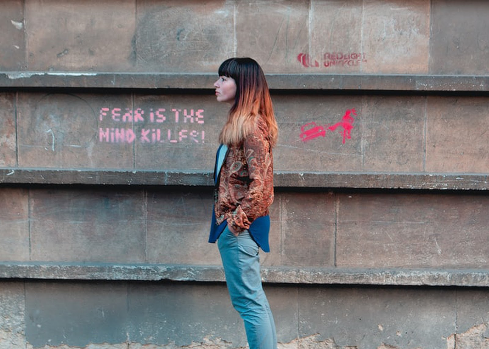 side profile of a woman alongside a wall with a motivational quote