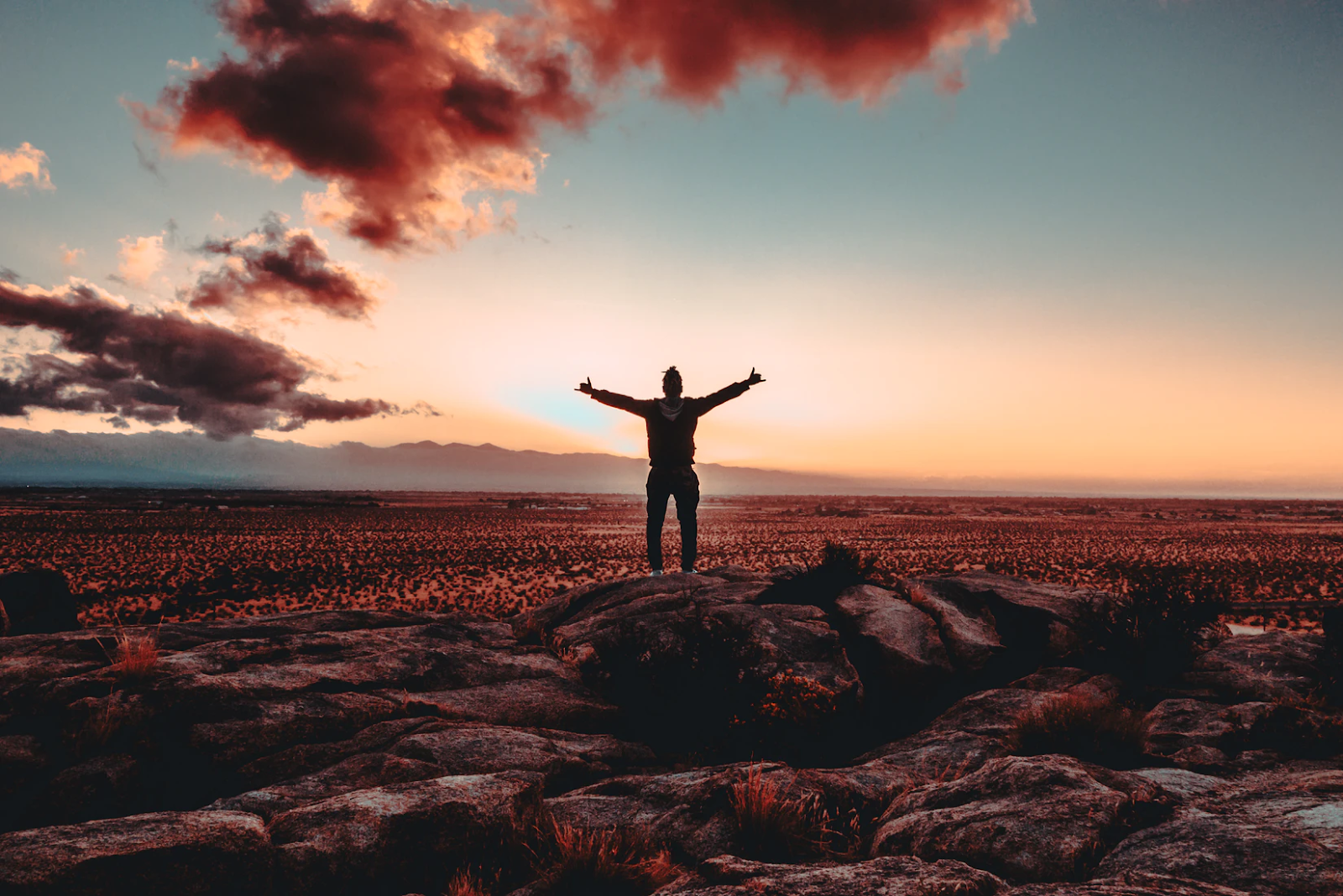person standing on top of a hill feeling triumphant