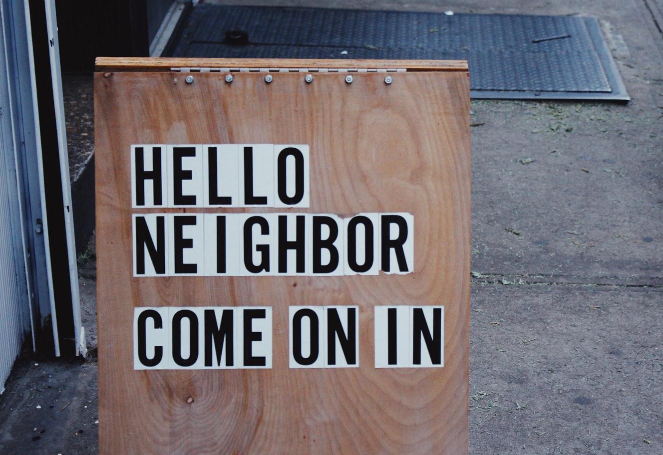 wooden sign welcoming neighbors in