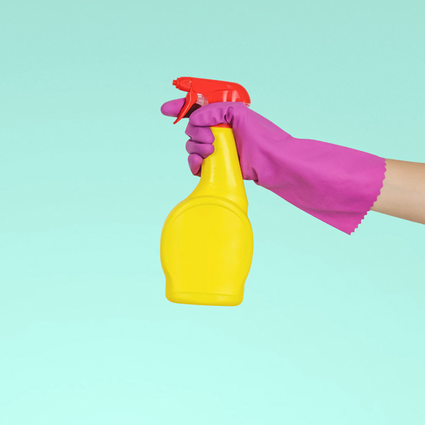 person wearing a glove and holding a disinfectant spray