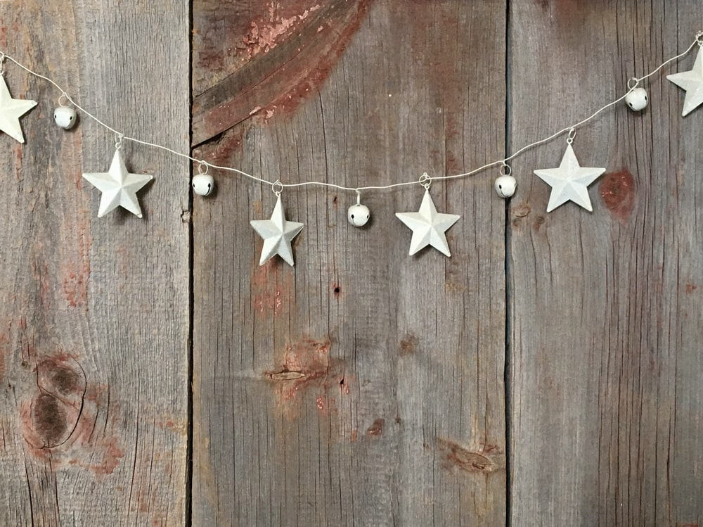 a string of stars and bells handing on a wooden fence