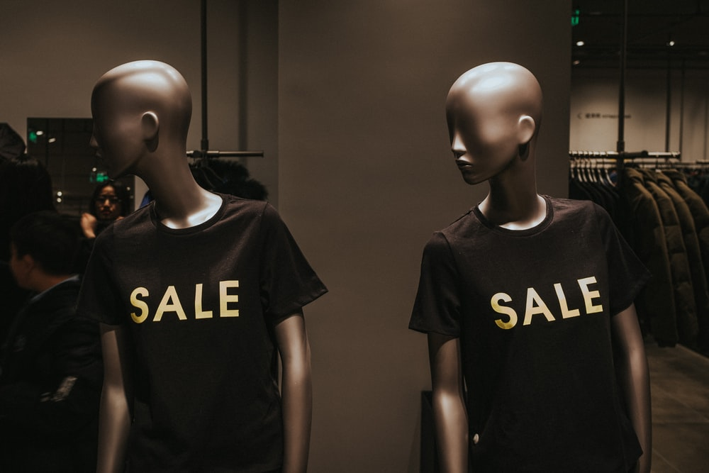 two mannequins wearing shirts that say sale