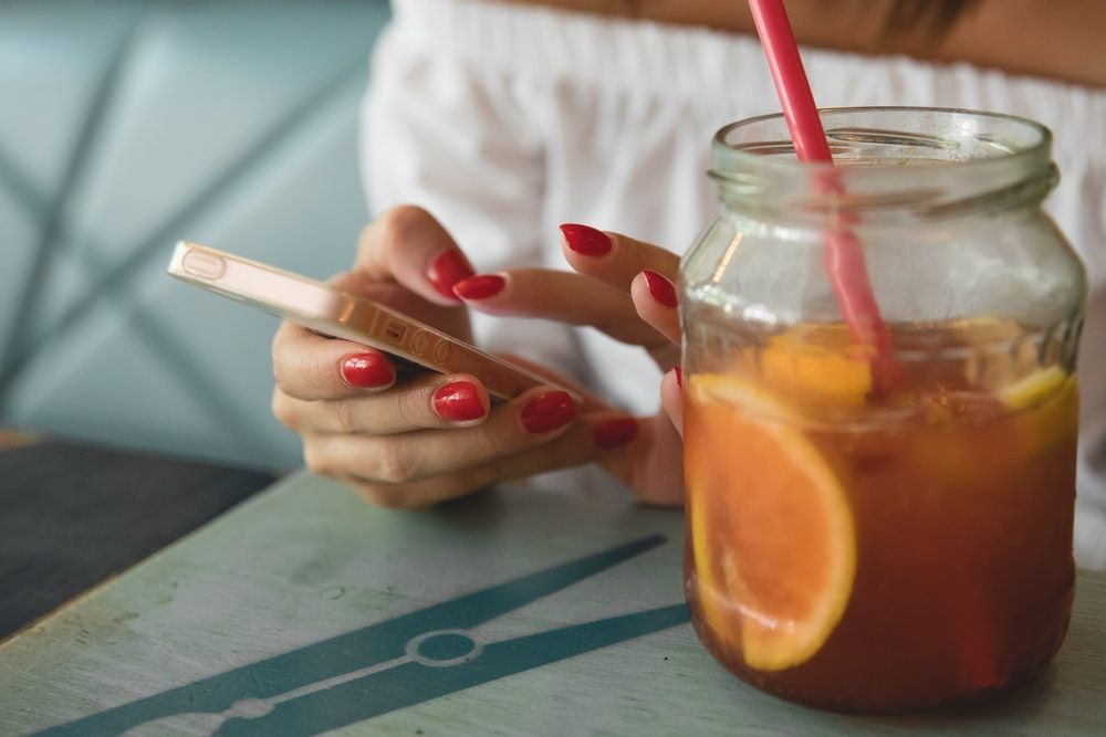 woman holding her phone next to a clear jar of fruit juice